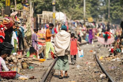 Person walking along train tracks in an Indian slum